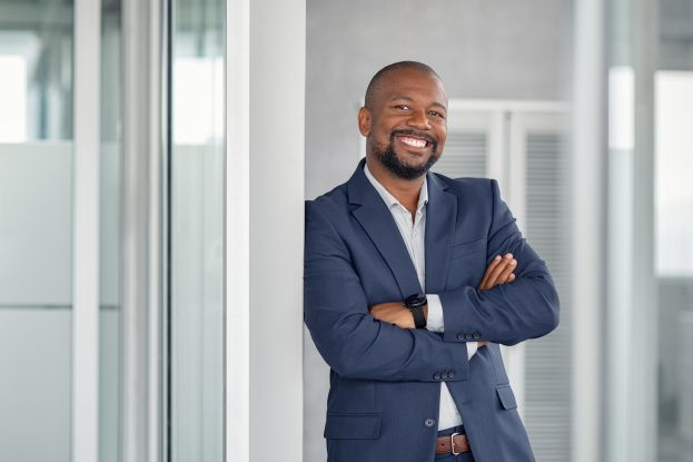 Mature cheerful african american executive businessman at workspace office. Portrait of smiling ceo at modern office workplace in suit looking at camera. Happy leader standing in front of company building.